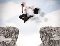 Uomo di affari divertenti che salta sopra le rocce con la lacuna Fotografia Stock