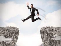 Uomo di affari divertenti che salta sopra le rocce con la lacuna Immagine Stock