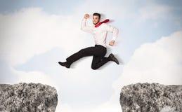 Uomo di affari divertenti che salta sopra le rocce con la lacuna Immagini Stock