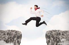 Uomo di affari divertenti che salta sopra le rocce con la lacuna Fotografia Stock Libera da Diritti