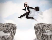 Uomo di affari divertenti che salta sopra le rocce con la lacuna Fotografie Stock Libere da Diritti