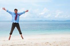 Uomo di affari divertenti che salta sulla spiaggia fotografia stock libera da diritti