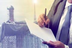 Uomo di affari ed alto progetto di costruzione della costruzione per il bene immobile Immagini Stock