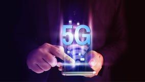 Uomo di affari facendo uso dello smartphone mobile con flusso delle icone 5G sul concetto dello schermo virtuale immagini stock