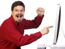 Uomo di affari maturi che indica al calcolatore fotografia stock