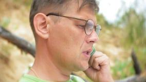 Uomo di affari maturi che parla sul telefono alla spiaggia vicino al mare archivi video