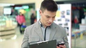 Uomo di affari nel centro commerciale facendo uso della compressa e del telefono archivi video