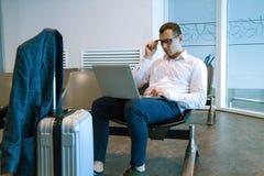 Uomo di affari nel funzionamento bianco su un computer portatile facendo uso di Internet di Wi-Fi in aeroporto immagini stock