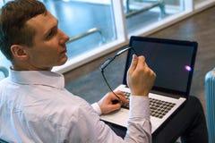 Uomo di affari nel funzionamento bianco su un computer portatile facendo uso di Internet di Wi-Fi in aeroporto fotografia stock libera da diritti