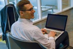 Uomo di affari nel funzionamento bianco su un computer portatile facendo uso di Internet di Wi-Fi in aeroporto fotografie stock libere da diritti