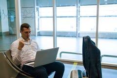 Uomo di affari nel funzionamento bianco su un computer portatile facendo uso di Internet di Wi-Fi in aeroporto fotografie stock