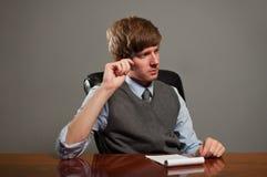 Uomo di affari nella riunione che pensa con il blocchetto per appunti Immagini Stock