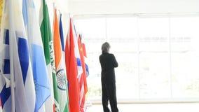 Uomo di affari o passeggiata del politico dal giusto angolo e supporto davanti alle bandiere internazionali archivi video