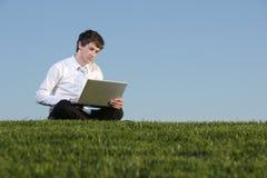 Uomo di affari su un computer portatile Immagini Stock