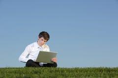Uomo di affari su un computer portatile Fotografie Stock Libere da Diritti