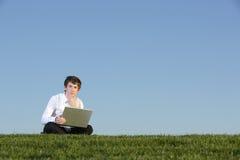 Uomo di affari su un computer portatile Immagine Stock Libera da Diritti