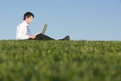 Uomo di affari su un computer portatile Fotografia Stock