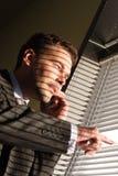 Uomo di affari sul telefono che osserva attraverso i ciechi di finestra fotografia stock libera da diritti