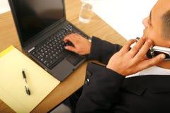 Uomo di affari sul telefono e sul calcolatore Immagine Stock