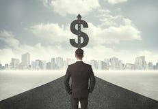 Uomo di affari sull'intestazione della strada verso un simbolo di dollaro Fotografia Stock Libera da Diritti