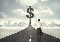 Uomo di affari sull'intestazione della strada verso un simbolo di dollaro Immagini Stock