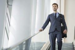 Uomo di affari sulla scala mobile Fotografie Stock Libere da Diritti