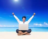 Uomo di affari sulla spiaggia con il computer portatile Fotografie Stock