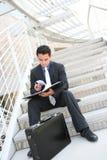 Uomo di affari sulle scale che esaminano le note Immagini Stock Libere da Diritti