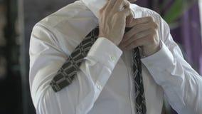 Uomo di affari in una camicia bianca che lega il suo legame stock footage