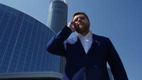 Uomo di affari in vestito blu che parla sul telefono sulla via 4K archivi video