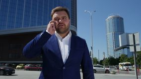 Uomo di affari in vestito blu che parla sul telefono sulla via 4K stock footage