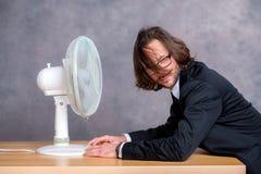 Uomo di affari in vestito scuro che si siede davanti al ventilatore immagine stock libera da diritti