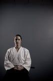 Uomo di Aikido con la meditazione di seduta di katana (spada) Fotografia Stock