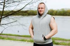 Uomo di allenamento in cappuccio che riposa dal fiume all'aperto Fotografia Stock Libera da Diritti