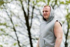 Uomo di allenamento nel riposo del cappuccio esterno Fotografia Stock