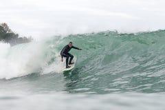 Uomo di 68 anni che pratica il surfing una grande onda fotografia stock