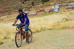 Uomo di Aymara che guida la bicicletta immagini stock libere da diritti