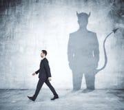 Uomo di camminata con l'ombra del diavolo immagine stock