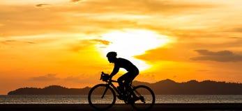 Uomo di ciclismo della siluetta alla spiaggia Fotografie Stock Libere da Diritti