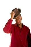 Uomo di colore in camicia rossa che capovolge un cappello del Brown Fotografie Stock