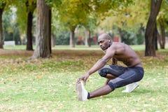 Uomo di colore che fa allungamento prima dell'correre nel fondo urbano Fotografia Stock Libera da Diritti