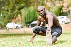 Uomo di colore che fa allungamento prima dell'correre nel fondo urbano Immagini Stock