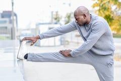 Uomo di colore che fa allungamento prima dell'correre nel fondo urbano Fotografia Stock