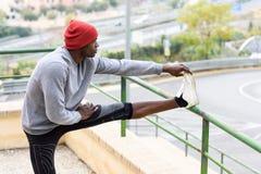 Uomo di colore che fa allungamento prima dell'correre nel fondo urbano Immagine Stock Libera da Diritti
