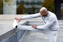 Uomo di colore che fa allungamento prima dell'correre nel fondo urbano Fotografie Stock Libere da Diritti