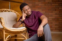 Uomo di colore che si siede sul pavimento e che esamina macchina fotografica Fotografie Stock