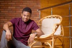 Uomo di colore che si siede sul pavimento e che esamina macchina fotografica Immagine Stock