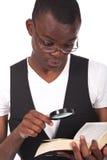 Uomo di colore che tiene una lente d'ingrandimento Fotografie Stock