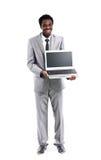 Uomo di colore felice che mostra computer portatile Fotografie Stock Libere da Diritti