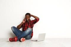 Uomo di colore felice che usando cellulare e computer portatile che si siede sul pavimento dello studio Fotografia Stock
